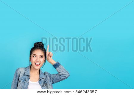 Happy asian woman feeling happiness and standing pointing hands up to copyspace on blue background.Cute asia girl smiling wearing casual jeans shirt and finger pointing to above for present promotions stock photo