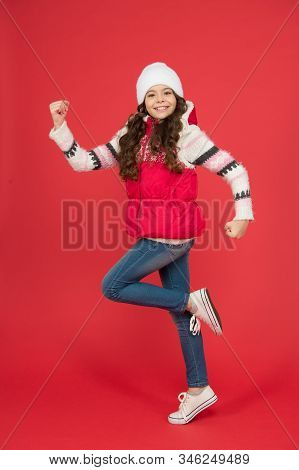 Active kid. Child in woolen knitted hat. Kids tend to feel cold more than adults. Winter fashion. Small girl long curly hair. Winter holidays ideas. Winter activity for kids. Happy childhood. stock photo