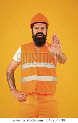 Caution, under construction. Hard worker showing caution sign on yellow background. Bearded man with caution hand gesture wearing protective workwear. Caution warning. stock photo