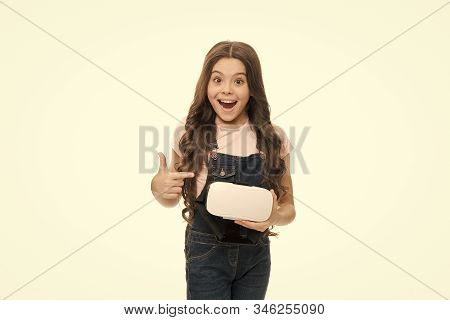 Brand presentation. Cyber gaming. Augmented reality technology. Virtual reality is exciting. Girl little kid hold vr glasses white background. Virtual education concept. Interaction in virtual space. stock photo