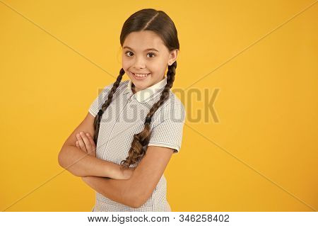 Confident in her knowledge. School lesson. Inspiration for study. Back to school. Knowledge day. Schoolgirl enjoy study. Kid school uniform. Smiling cutie crossed hands yellow background copy space. stock photo