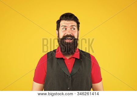 Happy face. Hospitality staff. Restaurant cafe staff wanted. Man bearded hipster with mustache wear vest shirt uniform yellow background. Shop staff concept. Salesman career. Hiring shop store worker. stock photo