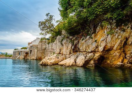 Cliffs near port and Sablicevo beach in Rijeka, Croatia. Rocky coast in the east of town with small beaches, hotels, buildings and cliffs covered with lush green trees. Steep stairs lead to water. stock photo