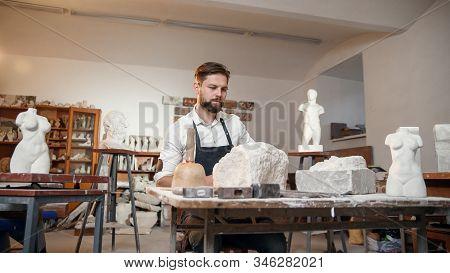 Male sculptor in white shirt and black apron makes a limestone copy of woman torso at the artistic studio. stock photo