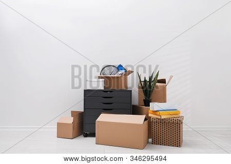 Cardboard boxes and packed belongings near white wall. Moving day stock photo