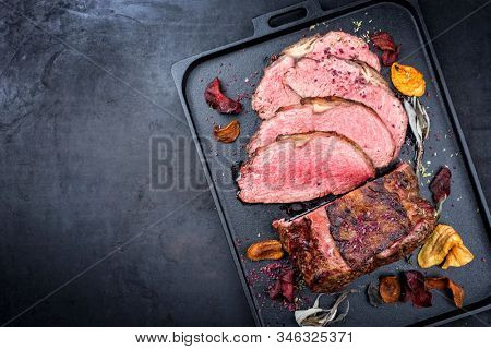 Traditional Commonwealth Sunday roast with sliced cold cuts roast beef with vegetable chips and herbs as top view on a modern design tray with copy space left  stock photo