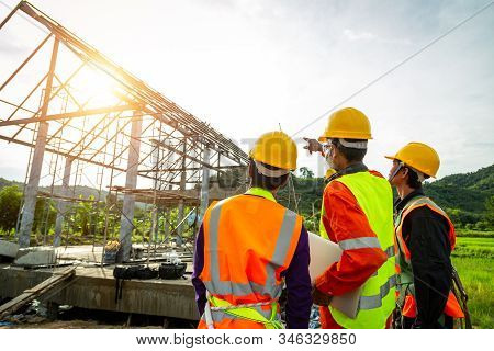 Engineer technician watching team of  worker control in Construction workers wearing safety clothing and discussing on construction site checking office laptop at construction site. stock photo
