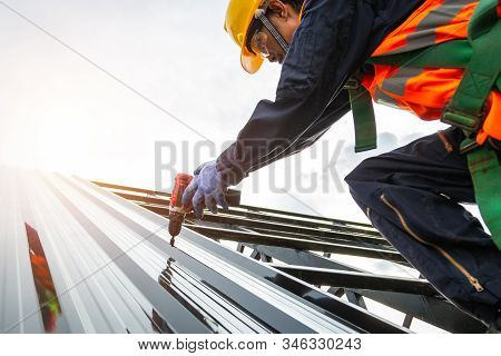 [Construction roof] Roofer worker in protective uniform wear and gloves, Construction worker install new roof,Roofing tools,Electric drill used on new roofs with Metal Sheet. stock photo