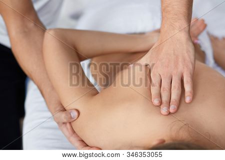 Young beautiful woman enjoying back and shouders massage in spa.Professional massage therapist is treating a female patient in apartment.Relaxation, beauty, body and face treatment concept.Home massage. stock photo