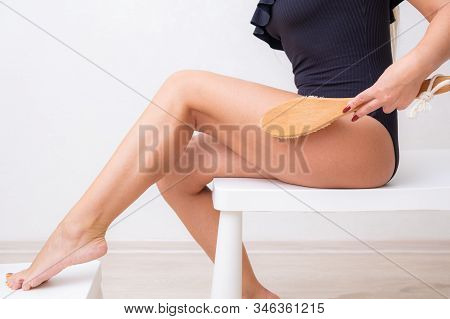 Beautiful Woman Making A Scrub Massage With Big Brush. Dry body brush, Woman dry brushing body to reduce cellulite, detoxify the lymphatic system, and achieve beautifully smooth skin. Dry skin brushing as part of morning health and energy routine. stock photo