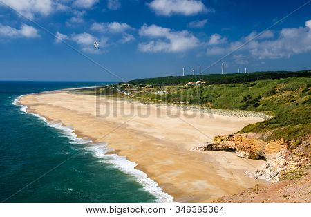 Portugal, Nazare in summer, coastline landscape of the Atlantic ocean in summer,  wide beaches with azure blue water of the Atlantica, cliffs of Nazare, dense greenery and windmills in the background stock photo