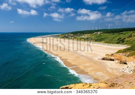Portugal, Nazare, Wonderful coastline landscape of Nazare beach in summer,  wide beaches with azure blue water of the Atlantic ocean, cliffs of Nazare, seagull flying in the sky stock photo