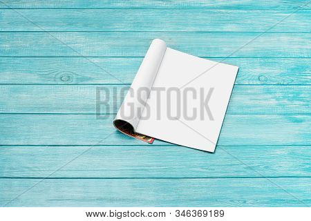 Mock-up magazine, newspaper or catalog on blue, wooden background. Blank page or notepad on planks backdrop. Blank page for mockups or simulations. stock photo