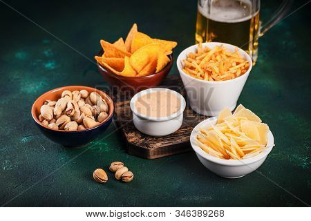 Assortment of unhealthy beer snacks: chips, nachos, pistachios, cheese in bowls, top view, copy space. Unhealthy eating concept. stock photo