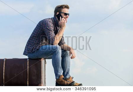 agile business. traveler wait for taxi. Move. macho man tourist relax tour bag. male fashion style. looking so trendy. businessman in glasses. business trip. sexy man sky background speak on phone stock photo
