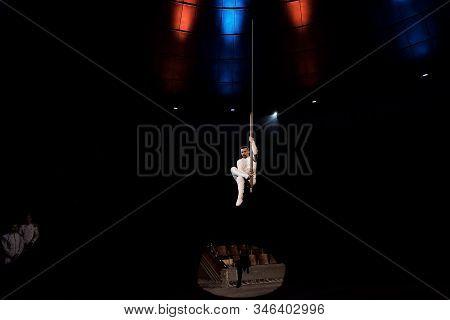 spotlights on acrobat performing acrobatic exercise on metallic pole in circus stock photo