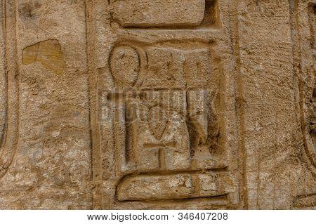 Egyptian ancient hieroglyphs on a stone wall. Closeup of symbol of eternal life ankh stock photo
