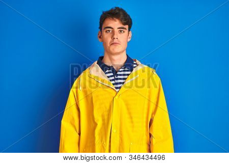 Teenager fisherman boy wearing yellow raincoat over isolated background depressed and worry for distress, crying angry and afraid. Sad expression. stock photo