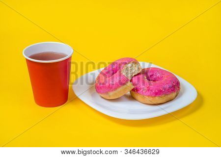 Two sweet half-eaten pink doughnuts on a white plate isolated on a yellow background. red disposable Cup of tea. Flat lay. The concept of unhealthy eating and weight gain. Harmful fast food.Copy space stock photo