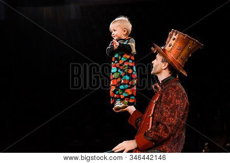 happy man holding adorable toddler kid in hand while performing in circus stock photo