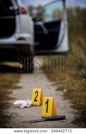 Crime scene investigation, bloody knife with crime markers on the ground, evidence of murder. stock photo