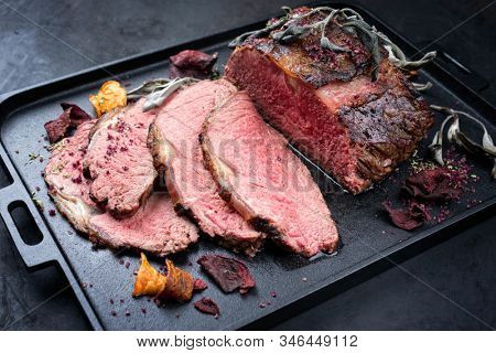 Traditional Commonwealth Sunday roast with sliced cold cuts roast beef with vegetable chips and herbs as closeup on a modern design tray  stock photo