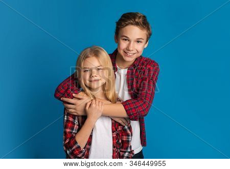 Siblings love. Portrait of happy kids brother and sister hugging and posing together over blue background in studio, free space stock photo