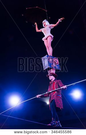 low angle view of man holding pole and supporting attractive acrobat while walking on rope stock photo