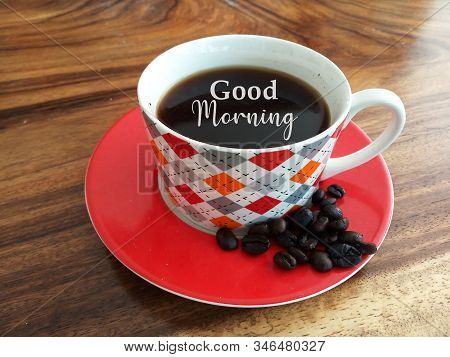 Morning coffee. A cup of black coffee and raw coffee beans with  text greeting - Good morning. On natural background of wooden table. Fresh morning with coffee drink concept. stock photo