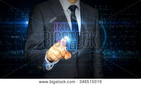 A businessman in a suit touch screen with industry 4.0 symbol hologram. Man using hand on virtual display interface. Innovation, cyber technology, ai, business and automate futuristic concept. stock photo