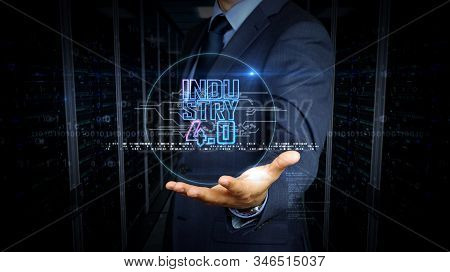 Man with industry 4.0 symbol hologram on hand. Businessman and futuristic concept of innovation, cyber technology, ai, business, digital tech and automate production. stock photo