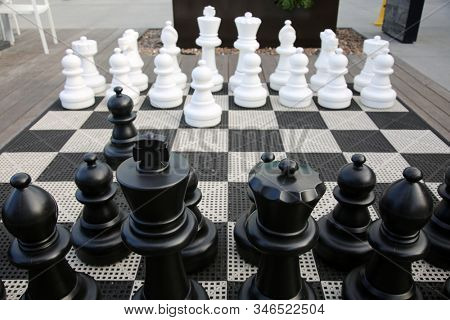 Chess Kit. Giant Chess Game in a public area. People can play a Giant Chess Game as they enjoy a nice day outside. Chess is a game that has been enjoyed for hundreds of years. stock photo