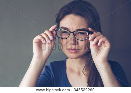 A woman with vision problems hold eyeglasses stock photo