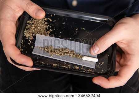 Man rolling a marijuana joint. Drugs narcotic concept. Close up of addict lighting up marijuana joint with lighter. Close up . Drug use. Man preparing and rolling marijuana cannabis joint. stock photo