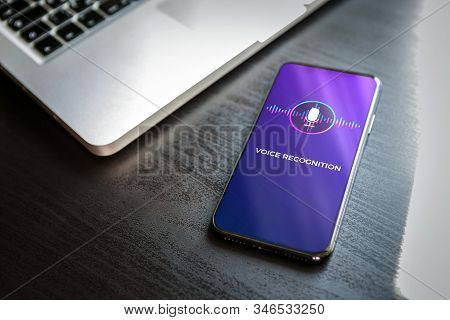 Voice recognition AI audio technology concept. Close-up smart mobile phone with a microphone and a wave icon on the screen. Virtual assistant app on smartphone stock photo