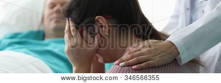Wife lost her husband in car accident and cries. Man lies in coma disconnected from the apparatus for maintaining life. Euthanasia donor make. Loss of a loved one concept stock photo