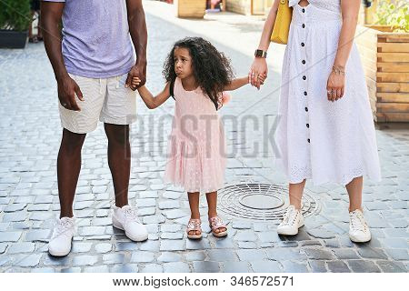 Happy multiethnic family from USA on their European vacation trip. White mother and black father holding hands with their adorable cute mixed race daughter in pink dress making face on summer street. stock photo
