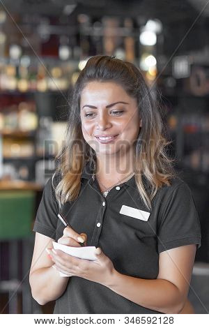 Waitress with a notebook takes an order. Waitress taking order on a notebook in pub. Waiter writing an order in bar af hotel. Staff, hospitality, good customer service concept. stock photo