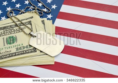 Army identification medallions and dollar bills on United states flag. Military pension, salary in the army or military insurance stock photo