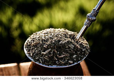mate bowl, outdoors. Yerba mate typical of Argentina, Brazil and Uruguay. Mountain scenery in the background. It consists of a gourd, a pump, ground yerba mate and warm water. stock photo