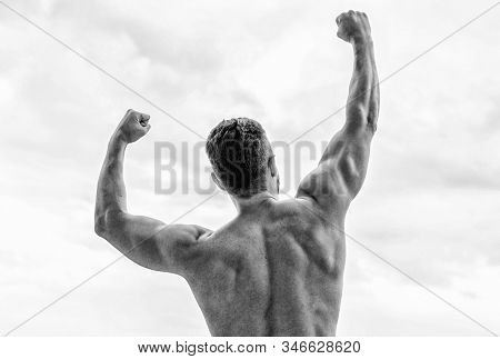 Victory and success. Champion and winner concept. Man celebrating success. Bodybuilder strong muscular body feeling powerful and superior rear view. Achieve success. Great shape. Successful athlete stock photo