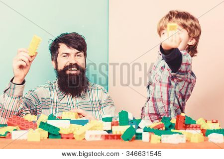 Father son game. Father and son create constructions. Bearded man and son play together. Every dad and son must do together. Dad and kid build plastic blocks. Child care development and upbringing stock photo