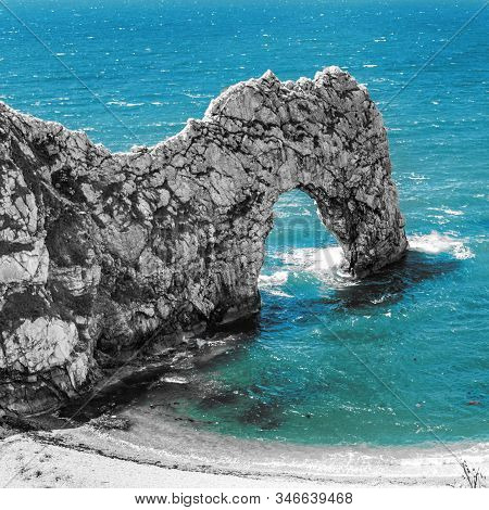 Durdle Door rock arch. Lulworth on the Dorset Coast in Southern England. With desaturated rock and blue sea. stock photo