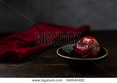 Art concept of the problem of food consumption. Red rotten apple on a plate with tehstil on a wooden table and a gray background. Minimalistic still life in a dark style of paintings by artists. stock photo