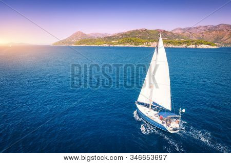 Aerial view of beautiful white sailboat in blue sea at bright sunny summer evening. Adriatic sea in Croatia. Landscape with yacht, mountains, transparent blue water, sky at sunset. Top view of boat stock photo
