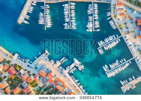 Aerial view of boats and yachts in port in old city at sunset. Summer landscape with houses with orange roofs, motorboats in harbor, clear blue sea, cars on the road. Beautiful architecture. Top view stock photo