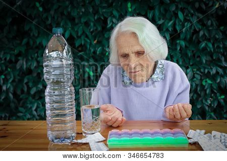 Closeup of beautiful 90 year old woman with pills on table. Elderly woman, with headache, emotional problem, dementia, mental disorder, frustrated. Elderly concept. stock photo