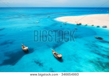 Aerial view of fishing boats on tropical sea coast with transparent blue water and sandy beach at sunny day. Summer holiday. Indian Ocean in Zanzibar, Africa. Landscape with boat, white sand. Top view stock photo