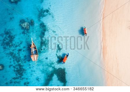 Aerial view of the fishing boats in clear blue water at sunset in summer. Top view from drone of boat, yacht, sandy beach in Zanzibar. Travel. Tropical seascape with sailboats, sea. View from above stock photo