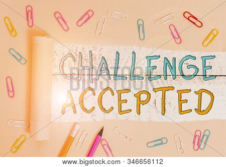 Text sign showing Challenge Accepted. Conceptual photo to participate or undertake in a competitive situation Stationary and torn cardboard placed above a wooden classic table backdrop. stock photo